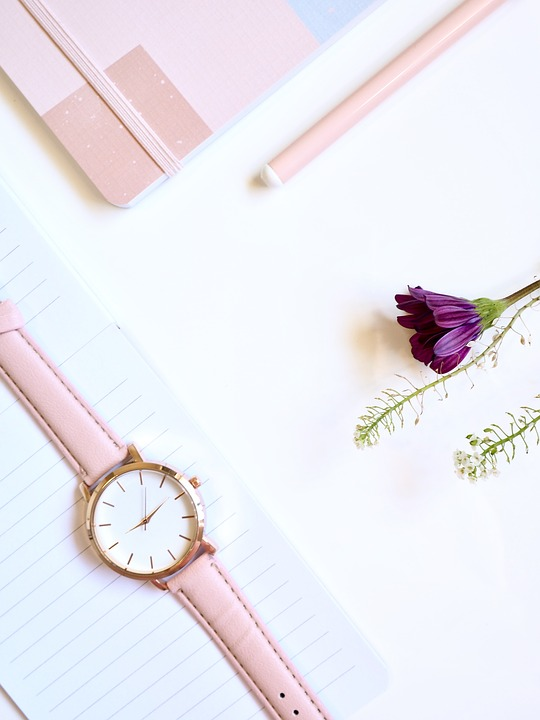 A flat lay image for a blog post about the importance of blog design with a white background of a lined note pad with a pink watch on top, a pencil and a purple flower