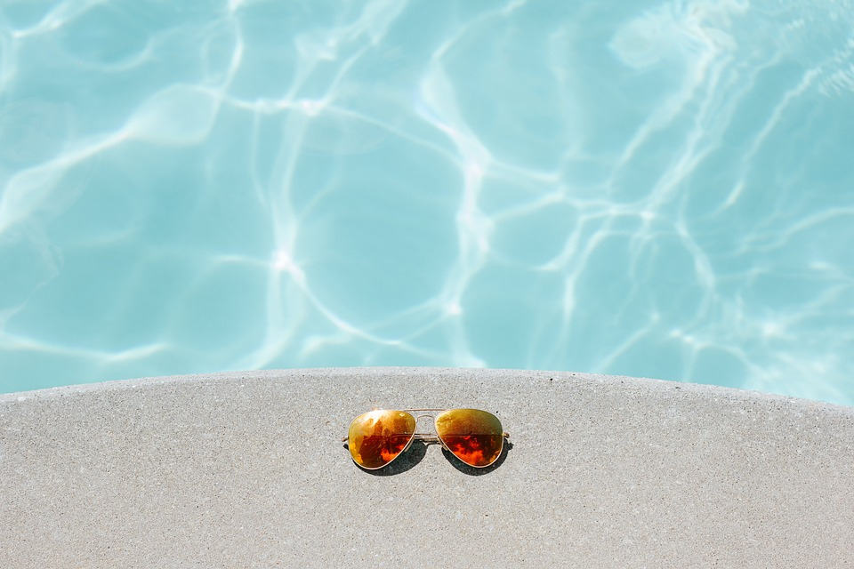 A pair of sunglasses by the side of a swimming pool