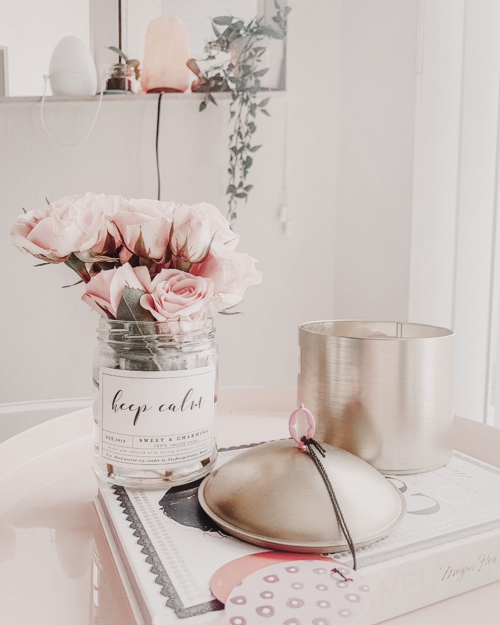 Desk with light pink flowers in a jar that says keep calm